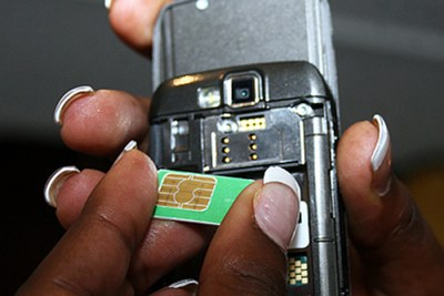 A mobile phone user inserts a SIM card into a phone.