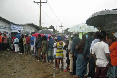 Liberians queue in the rain to cast their votes in 2011.