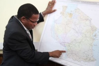 Minister for Foreign Affairs and International Cooperation, Bernard Membe points to a median line border between Tanzania and Malawi on a recent administrative map of Tanzania .