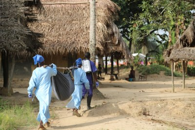 An MSF health team carrying a suspected Ebola patient from a remote hamlet (file photo).