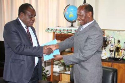 Richard Mibey (right), then vice-chancellor of Moi University, hands over to Laban Ayiro.