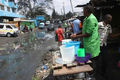 A food vendor goes about her business as raw sewage flows nearby.