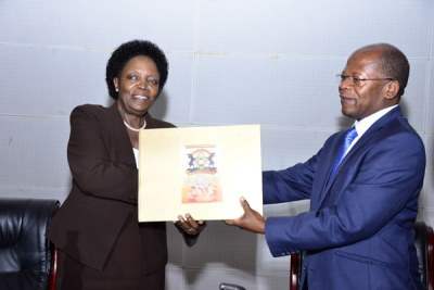 Uganda National Examinations Board chairperson Professor Mary Okwakol hands the 2017 Uganda Advanced Certificate of Education Examination results to State Minister for Higher Education Dr John Chrysostom Muyingo, right, in Kampala on February 21, 2018.