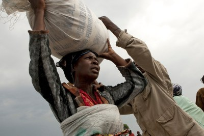 DR Congo: A woman carries a bag of food ration.