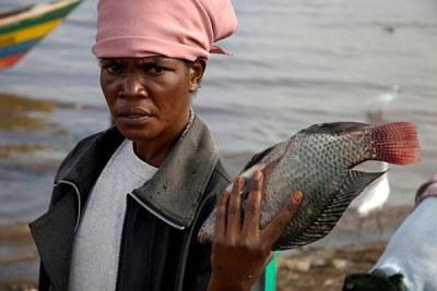 A woman displays fish in lake Victoria,Kenya.