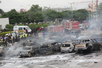 Fire fighters at the scene of the bomb blast at the Car Park, Police Force Headquarters, Abuja (file photo).