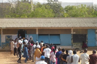 Voters line up outside a polling station.