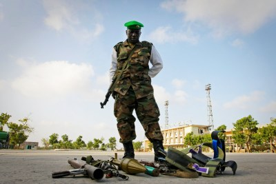A soldier stands over the weapons seized from four suspected members of Al Shabaab.