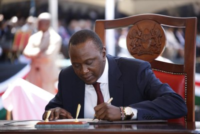 Uhuru Kenyatta Signing presidential oath infront of supportes and government dignitaries