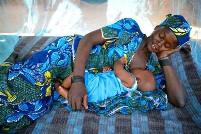 Une femme entrai d'allaiter son bébé.