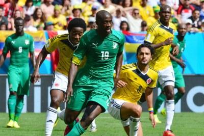(Photo d'archives) - Yaya Touré échappe à un tacle de Carlos Sanchez de la Colombie lors la Coupe du Monde Brésil 2014