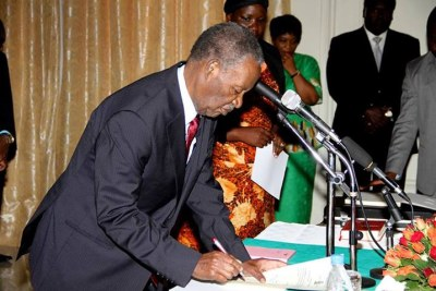 President Michael Sata signs a document.