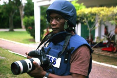 Barnus Sevi Gbekide wearing safety equipment while taking photos during the post-election crisis.