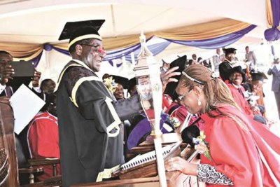 President Mugabe caps his wife Grace during  graduation.
