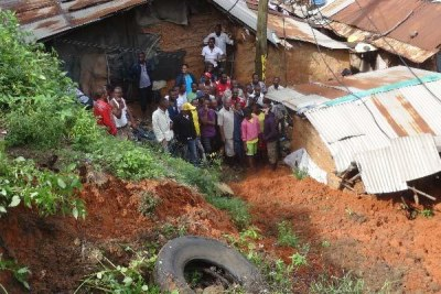 Locals mill around a house which had collapsed and killing one person on spot over ongoing heavy rain at Kalahari Changamwe Mombasa.