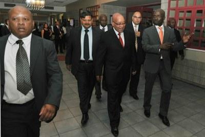Le président Zuma accompagné d'Atul Gupta, ministre des Entreprises publiques Malusi Gigaba et président-directeur général du New Age Nazeem Howa lors du petit-déjeuner d'affaires New Age à Port Elizabeth.