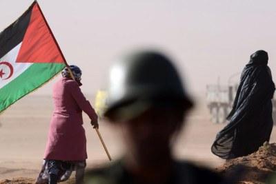 Une Sahraouie porte un drapeau du Front Polisario