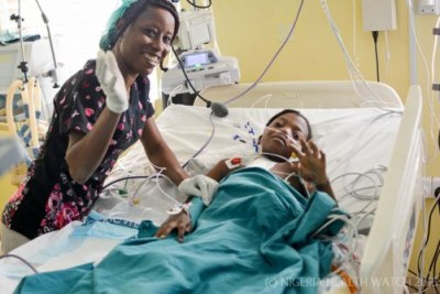 A young patient waves as she recovers in the Pediatric ICU after her heart surgery procedure.