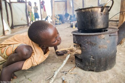 A Burudian child prepares a meal at Mahama refugee camp. Environmentalists are warning about the dire effects of cutting trees for firewood.