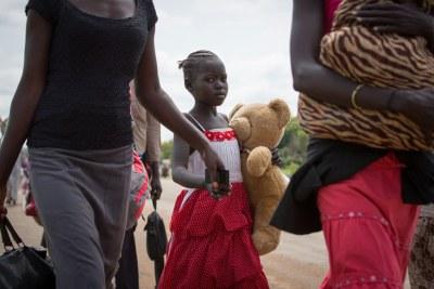 Une jeune réfugiée et sa famille traversent la frontière entre le Soudan du Sud et l'Ouganda.