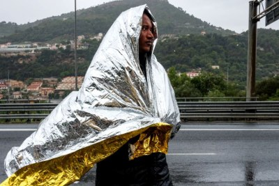 A man from Eritrea walks along the road after leaving a Red Cross Caritas camp set up for migrants in the Italian border town of Ventimiglia, Italy, Oct. 13, 2016