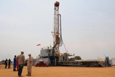 Workers discuss at an oil rig in the Albertine Graben area. Government is yet to start oil production.