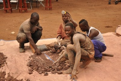 Miners searching for gold from the dust collected from a gold pit in Kasanda-Mubende