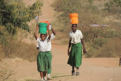 Some of the girls carrying buckets of water to school.