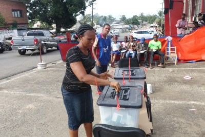A woman casts her ballot at a polling center situated on Monrovia's Tubman blvd
