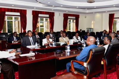 President Yoweri Museveni, left, in discussion with the parliament's legal affairs committee led by Oboth Oboth, second left.