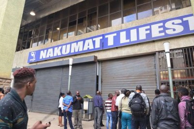Employees and bystanders mill around the entrances to Nakumatt Lifestyle branch on Hazina Towers in Nairobi after it was shutdown on December 22, 2017 over unpaid rent arrears.