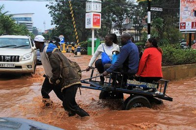 Nairobi residents are taken across a flooded section of Peponi Road last week.