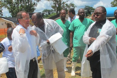 A UN representative and DR Congo officials examine the impact of the virus in 2014.