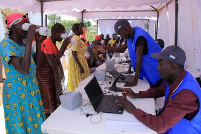 Verification. World Food Programme officials register refugees using a biometric verification system at Imvepi Refugee Settlement Camp in Arua District.