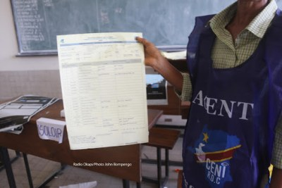 An election worker shows a set of results after the December 30 vote.