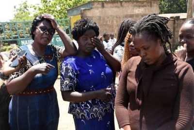 Carolyne Odira (left), Mildred Odira's mother, Maureen Anyango (right), Mildred's sister, and other family members outside City Mortuary on February 4, 2019.