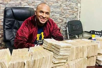 Zaheer Merhali Jhanda poses with bunches of cash. He has been roped into the fake gold trade.