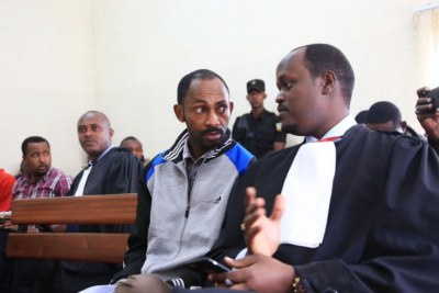 Callixte Nsabimana (left) consults his lawyer Moise Nkundabarashi in court.