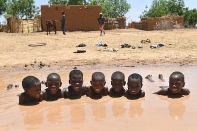 Des garçons prennent un bain dans une marre à Zinder, dans le centre du Niger.