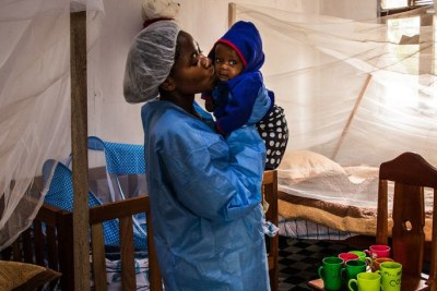A caregiver with the seven-month-old baby of a woman who died of Ebola in North Kivu (file photo).
