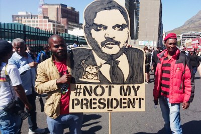 A protest placard depicting Atul Gupta carried by two EFF members at a Zuma Must Fall protest in Cape Town (file photo).