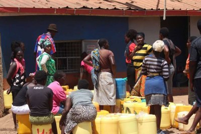 People wait to buy water from a local vendor (file photo).