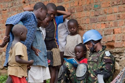 A peacekeeper from the MONUSCO Force Intervention Brigade in the town of Pinga, North Kivu province, spends time with local children in December 2013. Pinga is located 148 km northwest of Goma, the provincial capital at the Rwandan border. At the time, Pinga haS been recently vacated by the local militia NDC (Nduma Defense of Congo) led by the rebel Ntabo Ntaberi Sheka.