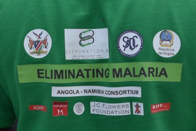 A health worker, testing children for malaria along Namibia's border with Angola, wears a t-shirt showing the collaborative effort of the Elimination 8 campaign.